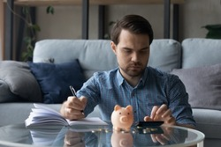 Serious millennial man calculating savings, counting budget after paying bill, taxes, mortgage fees, making notes at table with piggy bank, cash. Homeowner doing bookkeeping work. Finance concept