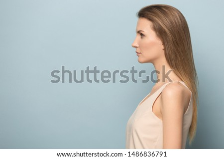 Photo of Serious millennial woman with long blonde hair stand profile isolated on blue studio background look at blank copy space aside, focused young female model feel confident at side view portrait image