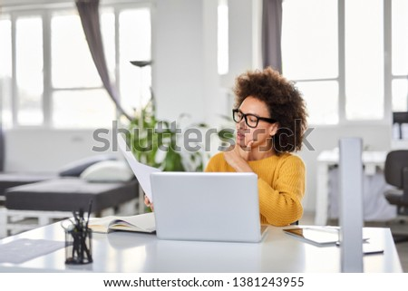 Serious mixed race attractive businesswoman dressed smart casual holding paperwork while sitting in modern office. #1381243955