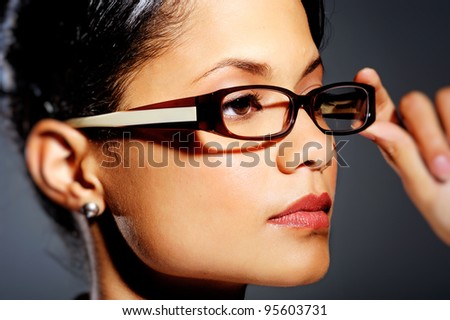 Serious mixed race woman looking away while she holds her glasses