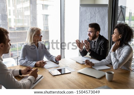 Serious multi-ethnic business entities gathered together for negotiating meeting lead by Arabian and aged businesspeople talk express opinion offer solutions solve current issues, partnership concept