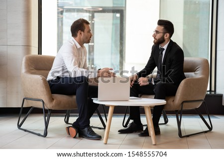 Serious multiethnic male business partners talk discussing potential cooperation or shared project, concentrated successful international businessmen speak brainstorm at meeting or briefing in office