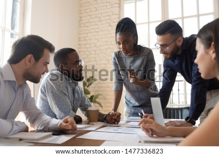 Serious multiracial corporate business team and black leader talk during group briefing, focused diverse colleagues brainstorm discuss report paperwork engaged in teamwork at meeting gather at table