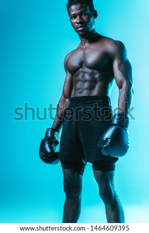 serious, muscular african american boxer looking at camera on blue background