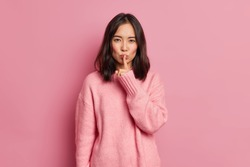 Serious mysterious brunette Asian woman presses index finger to lips makes hush gesture tells secret asks to be quiet wears long sleeved jumper poses against pink background. Secrecy concept