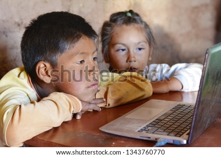 Serious native american kids using notebook.
