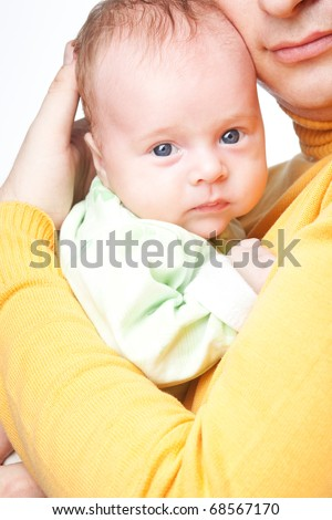 Serious newborn baby looking at camera while father hugging it and holding in his hands isolated over white background. Happy father likes his son.