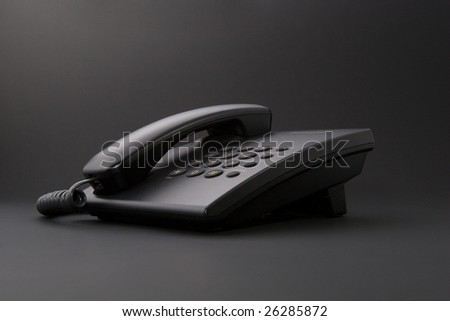 Serious office tool - black corded phone isolated on black background