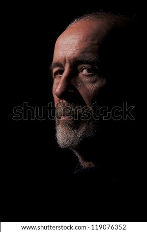 serious old man senior in light ray on black background