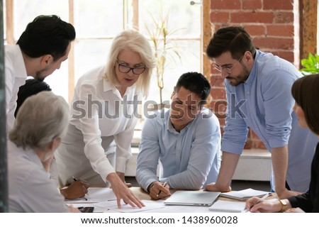 Serious old mature woman team leader coach teach young workers explain paper business plan at group meeting, focused senior female teacher mentor training diverse staff at corporate office workshop