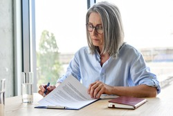 Serious older lawyer businesswoman in glasses reading signing trust partnership contract sit at table in office. Executive ceo put signature make legal bank sale financial loan investment agreement.