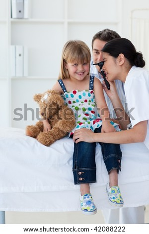 Serious patient examing littl girl's ears during a visit
