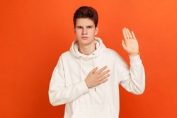Serious patriotic male in white sweatshirt with hood holding hand on heart, juryman swearing to speak truth in court, honor and conscience. Indoor studio shot isolated on orange background
