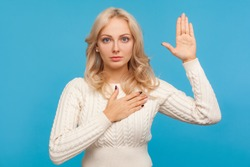 Serious patriotic woman with curly blond hair raising one arm and putting on chest another making oath, swearing. Indoor studio shot isolated on blue background