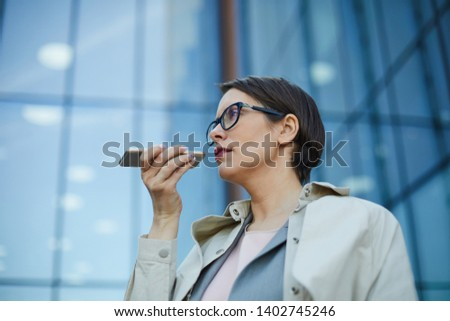Serious pensive confident middle-aged businesswoman in eyeglasses standing against office building and using smartphone while recording voice message