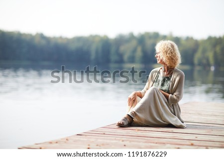 Serious pensive curly-haired mature lady in long skirt sitting on pier and contemplating tranquil nature around