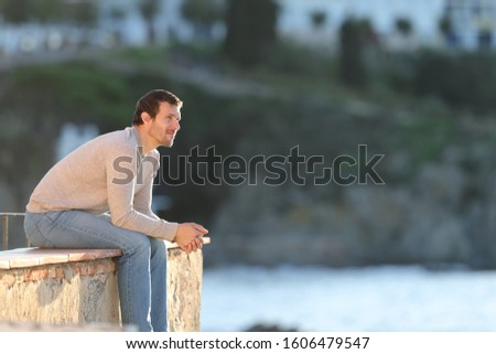 Serious pensive man contemplating views sitting in a balcony outdoors in a coast town on the beach