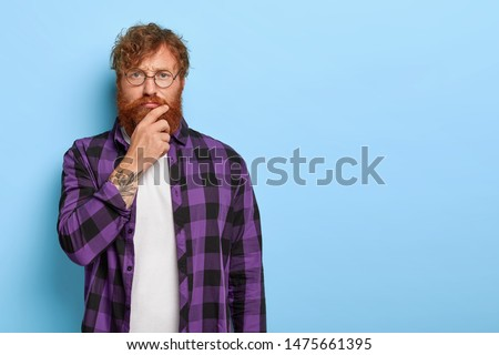 Serious pensive man scowls eyebrows and touches chin, being deep in thoughts, thinks over future plans, wears optical glasses and plaid purple shirt stands indoor against blue wall. Facial expressions