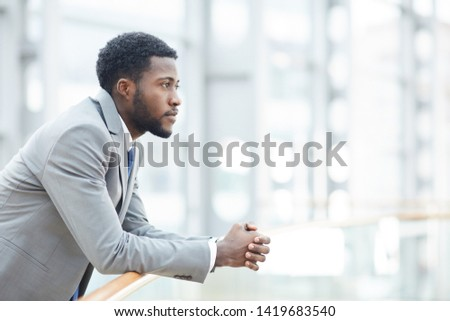 Serious pensive young black businessman with beard leaning on railing and planning new project