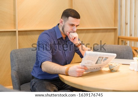 Serious pensive young man reads newspaper.