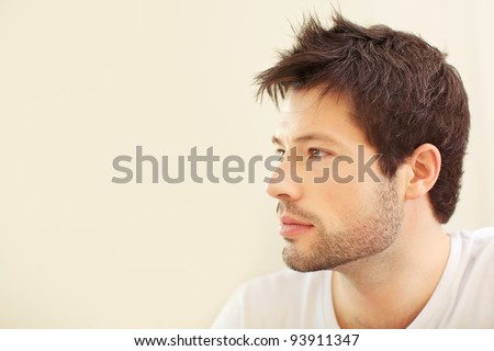 Serious pensive young man sitting in profile with copyspace, close-up face. - stock photo