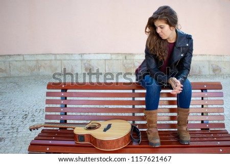 Serious pensive young woman looking at guitar while sitting on bench outdoors. Introspective girl in leather jacket thinking about music. Lifestyle concept