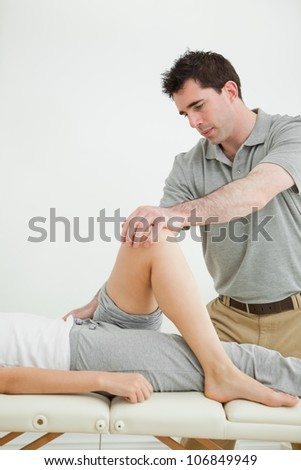 Serious physiotherapist stretching a leg while standing in a room - stock photo