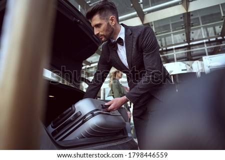 Serious porter wearing a suit angling toward a car trunk aiming to lift and take out a heavy suitcase Сток-фото ©
