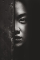 serious portrait of half face of asian woman blackandwhite