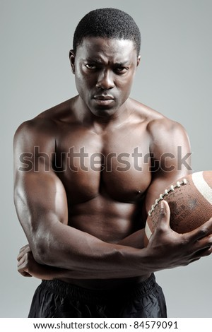 Serious portraits of a black american football sportsman in studio