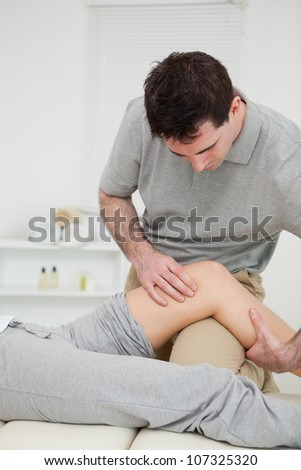 Serious practitioner holding the knee of a patient in a medical room