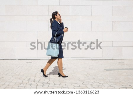 Serious professional late for work an drinking takeaway coffee on run. Young business woman in formal suit walking outdoors, carrying handbag and takeaway coffee. Morning way to office concept
