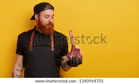 Serious professional male cook buys meat on rib for preparing dinner, has good reputation in restaurant, nice feedback from visitors, cooks his speciality dish, models over yellow wall with free space