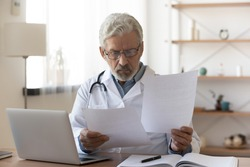 Serious professional senior elderly doctor doing paperwork checking medical documents at workplace. Concentrated old physician reading medic form analyzing patient diagnosis or report in hospital.