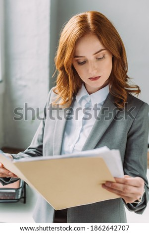 Serious redhead businesswoman in formal wear looking at folder with documents on blurred background ストックフォト ©
