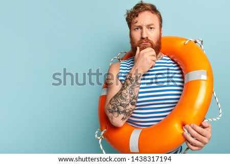 Serious redhead rescuer holds chin, has contemplative look, carries lifering, has tattooed arm, thinks abou safety swim, wears sailor vest, stands against blue wall, blank copy space. Vacation at sea Stok fotoğraf ©