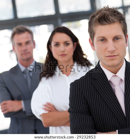 Serious Resolute and Confident Businessman in from of team - stock photo