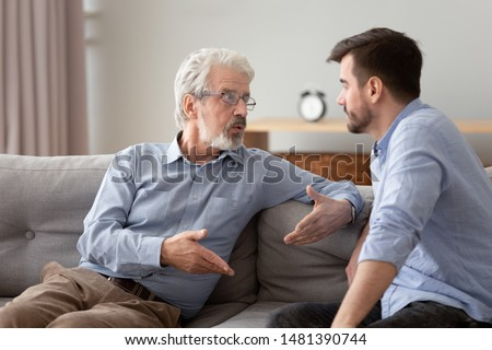Serious 60s elderly father and grown up adult son sitting on sofa talking having important conversation trying to solve life issues problem, different men relative people communication at home concept