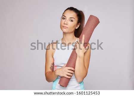 Serious sad tired woman in slim fit wear, has morning training in gym, hates sport, exercises alone. Fitness female holds rolled yoga mat, being ready for aerobic course. Healthy lifestyle, strength.