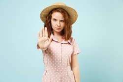 Serious sad young redhead curly woman 20s showing stop gesture with palm wears casual pink dress straw hat look camera isolated on pastel blue color background studio portrait. People emotions concept