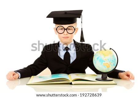 Serious schoolboy in academic hat sitting at the table with a book and globe. Isolated over white.