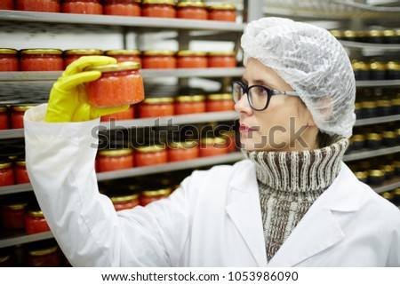 Serious seafood expert in protective uniform looking at jar with red caviar and checking quality of packing