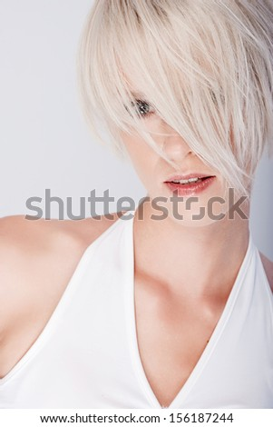 Serious seductive beautiful young blond with a modern hairstyle looking through the strands of her fringe with one eye fixed on the camera and parted lips