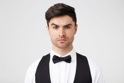 Serious self-confident attractive brunet with small stubble looks confidently, quizzically, incredulously, one eyebrow raised, smartly dressed, isolated over white background