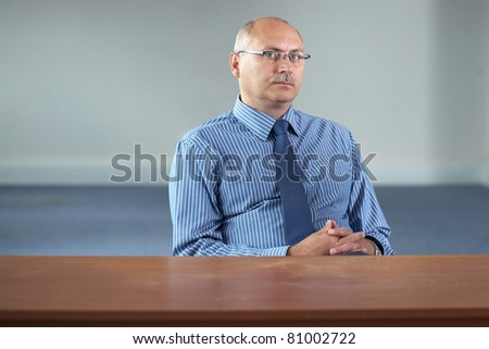 serious senior businessman sits behind empty desk, office shoot