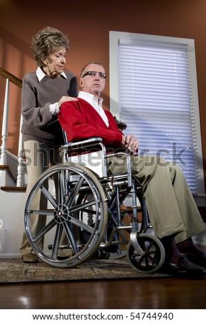 Serious senior couple at home, man in wheelchair