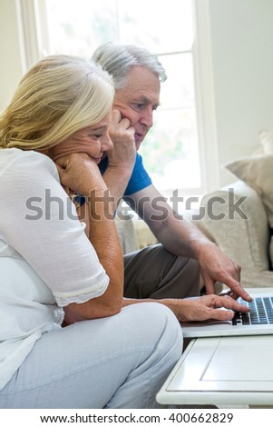 serious senior couple using laptop while sitting in living room at home #400662829