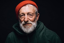 Serious senior grey-bearded fishman with wrinkled weathered face, puffy sad eyes looking at camera with mournful expression. Old man wears orange warm hat and green sweatshort posing over black wall.