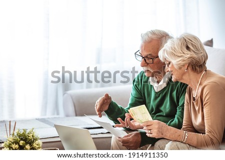 Serious senior husband and wife doing their home financials in the living room. Senior couple taking care of bills. Senior couple going over their household finances on a laptop