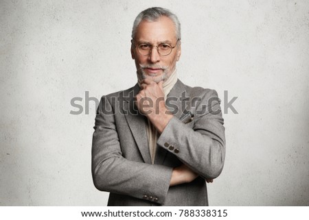 Serious senior male magnat dressed in formal suit, round spectacles, keeps hands crossed, listens attentively financial report, isolated over white concrete background. Pensioner poses indoor #788338315